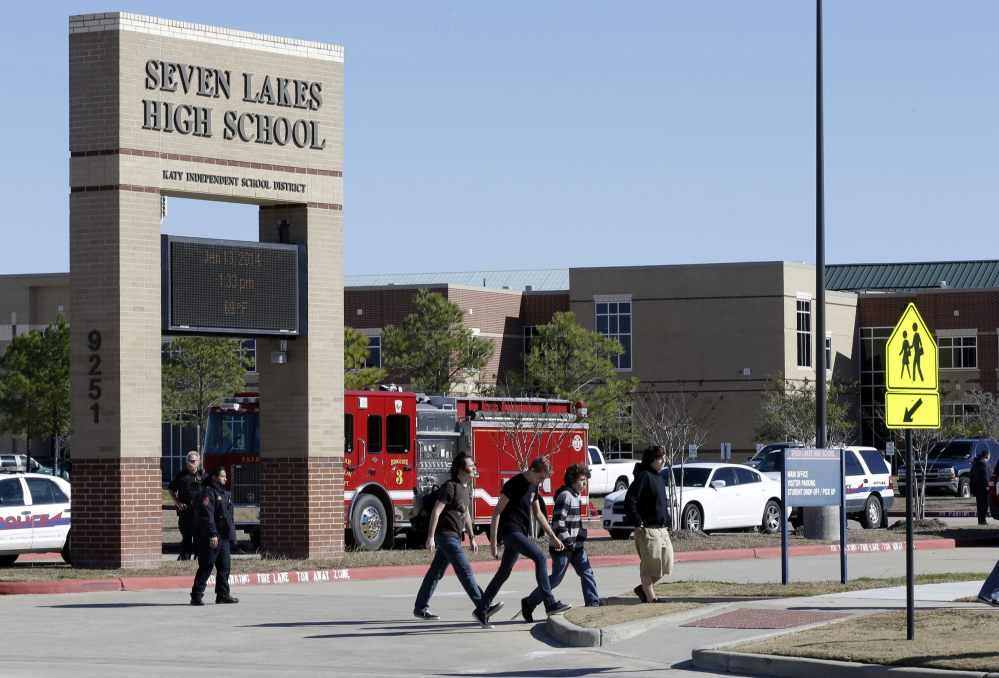 Students pass by Seven Lakes High School in Katy, Texas, after being evacuated and released from school for the day after a bomb squad was called to the school after a potentially explosive device was found.