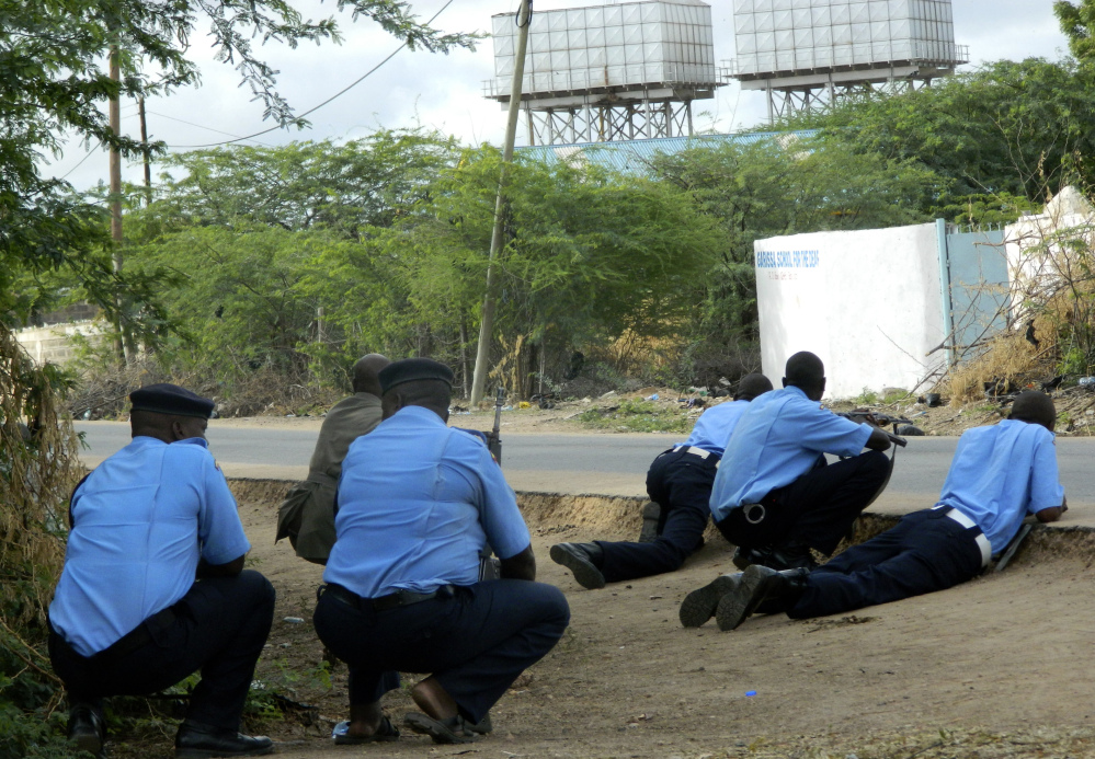 Kenyan police officers take cover outside the Garissa University College during an attack by gunmen Thursday. Islamist militants shot indiscriminately in campus hostels, killing 147.