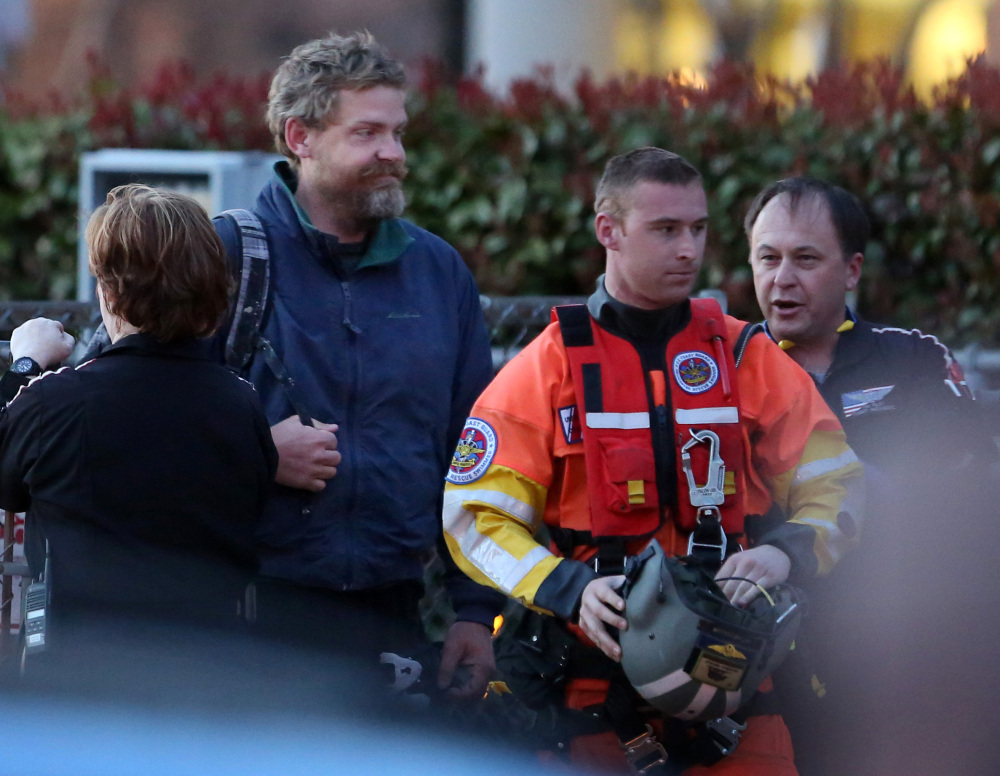 Louis Jordan, with beard, walks from the Coast Guard helicopter to the Sentara Norfolk General Hospital in Norfolk, Va., after being found off the North Carolina coast Thursday. His family says he sailed out of a marina in Conway, S.C., on Jan. 23, and hadn't been heard from since.