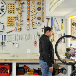 Steven Thurlow, age 12,  gets training from Andy Greif at the Community Bicycle Center in Biddeford. The group recently moved into a larger facility that  allows for tool display on the walls and plenty of space for the kids to fix bikes and learn life lessons like courtesy, responsibility, hard work and problem solving, according to Greif, the executive director.
