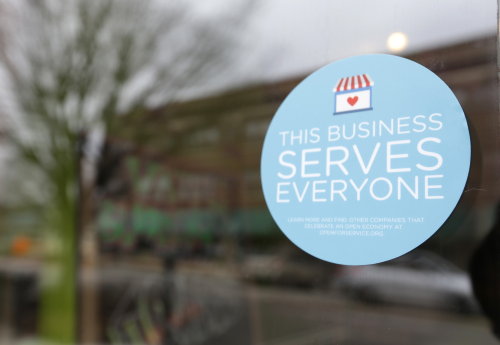 """FILE - In this March 25, 2015 file photo, a window sticker promising service to all is displayed in opposition to the state new religious objections law in downtown Indianapolis. Tourism agencies in Indianapolis and Fort Wayne are rolling out campaigns to tout the fact that """"All Are Welcome"""" in Indiana, but it might not be enough to completely heal the black eye the state received over its nationally-criticized religious objections law."""