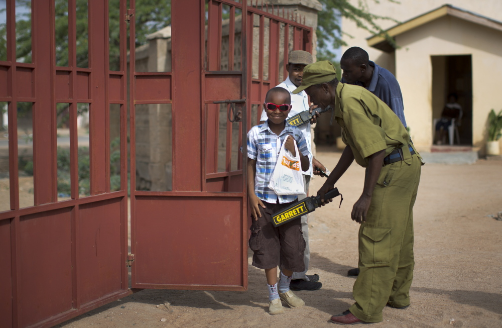 A young boy is frisked with a metal detector and has his bag searched near Our Lady of Consolation Church in Garissa, Kenya, on Sunday.