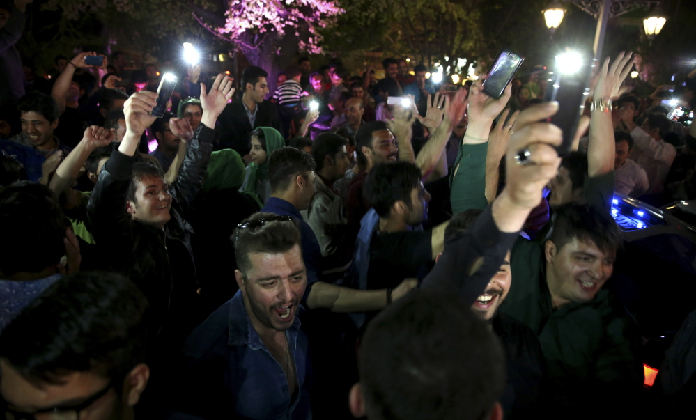 Iranians celebrate a framework agreement on Iran's nuclear program between their country and six world powers in Tehran on Friday.