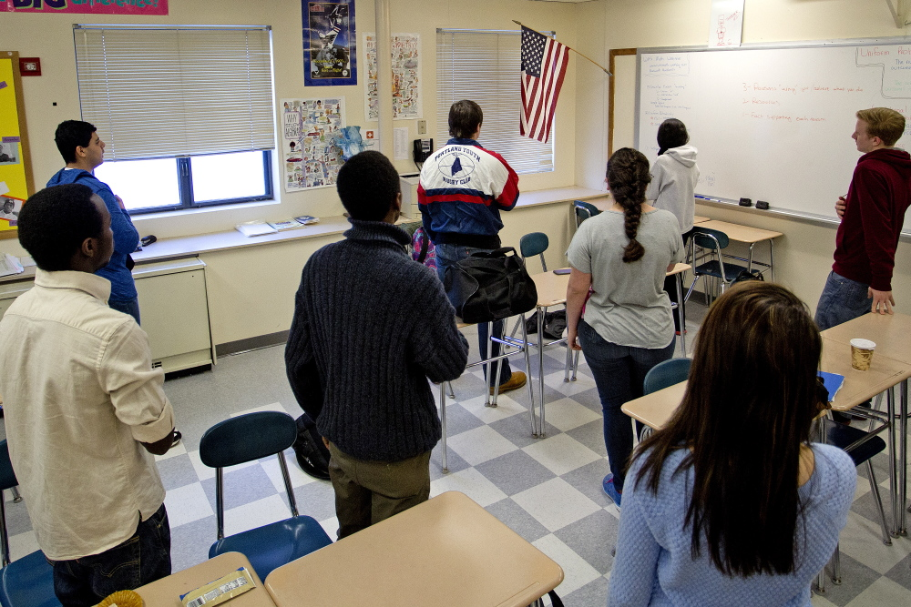 Students in the homeroom of Will Leque, a mathematics teacher at Westbrook High School, recite the Pledge of Allegiance before the start of school.