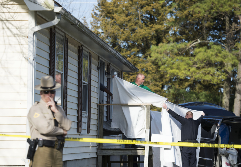 Sheets are held as a body is removed from the home where police say seven children and one adult were found dead Monday in Princess Anne, Md. Officers were sent to the home after being contacted by a concerned co-worker of the adult.