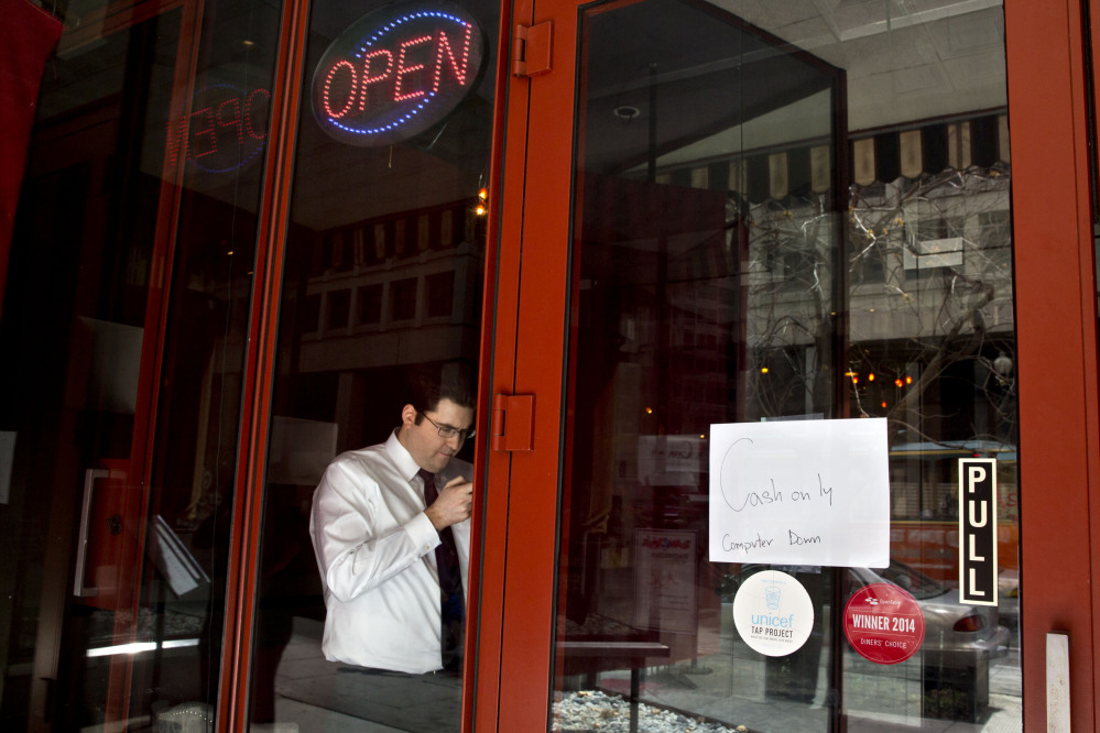 A man checks his cellphone in a restaurant with a sign advertising that the computer is down, as power returns after a brief power outage Tuesday in Washington.