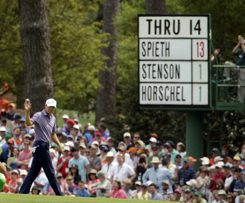 Jordan Spieth holds up his ball after making a birdie on the 15th hole, where the board shows him far ahead of his playing partners Friday in the second round of the Masters.
