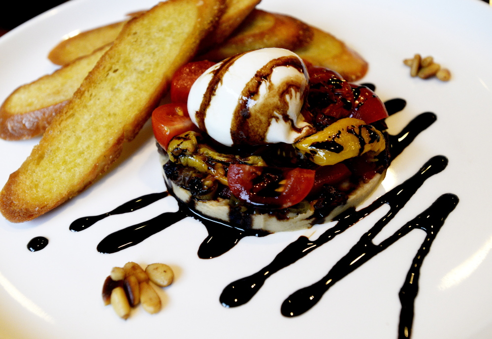Eve's comforting burrata appetizer features the cheese served atop cherry tomatoes and olives with a sprinkling of pine nuts.