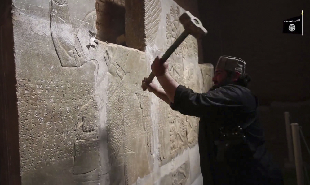 """An Islamic State militant takes a sledgehammer to an Assyrian relief at the site of the ancient city of Nimrud in this image from video posted late Saturday. The destruction follows other attacks on antiquities carried out by the group. The attacks have horrified archaeologists and U.N. Secretary-General Ban Ki-moon, who called the destruction at Nimrud """"a war crime."""""""