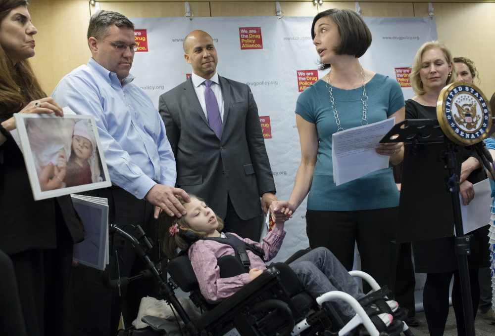 Polly VanderWoude holds the hand of her daughter Olivia, who suffers from severe epilepsy, as she advocates for a law that would allow access to marijuana extracts.