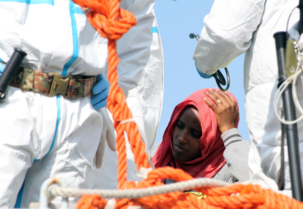 A woman waits to disembark from an Italian Navy vessel in southern Italy after being rescued in the Mediterranean, as workers in protective jumpsuits process incoming migrants.