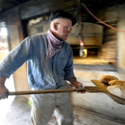 Mark Mickalide, 59, takes fresh bread from his brick oven at Black Crow Bakery in Litchfield. He bakes 750 loaves each week, available at the bakery and just eight other locations statewide.