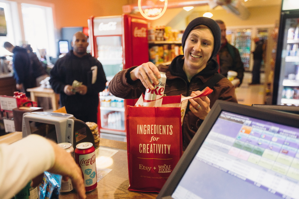"""Morgan McCormack places soda into a reusable bag at Colucci's Hilltop Superette on Congress Street on Monday. McCormack says she brought reusable bags to the store prior to the city's new policy, but the new fee is """"definitely a reminder."""""""