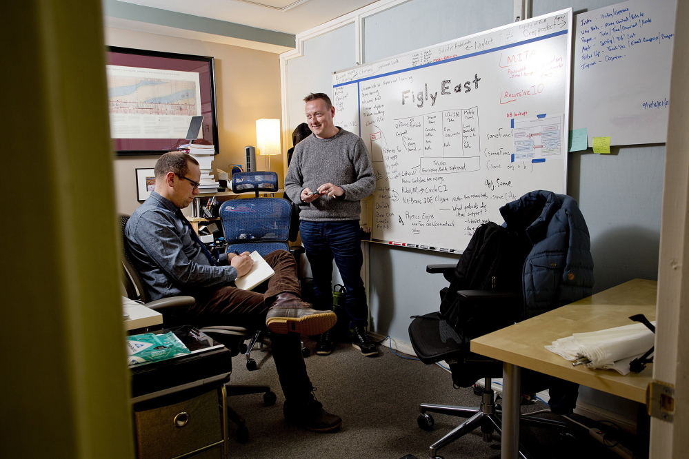 Elliot Murphy, right, who works for a San Francisco-based startup, and Abe Fettig, a senior architect, confer in their office space at Think Tank in downtown Portland. Murphy took his high-tech job with him to Portland when he moved here from Florida.