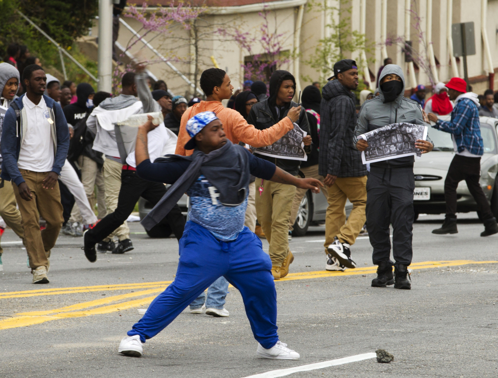Demonstrators throw rocks at police after the funeral of Freddie Gray on Monday at New Shiloh Baptist Church in Baltimore. Gray died from spinal injuries about a week after he was arrested and transported in a Baltimore Police Department van.