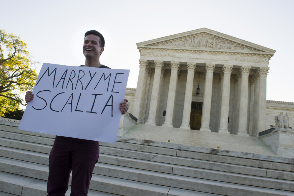 Ryan Aquilina, 24, of Washington holds a sign in front of the Supreme Court in Washington on Tuesday, as justices were set to hear historic arguments in cases that could make same-sex marriage the law of the land.
