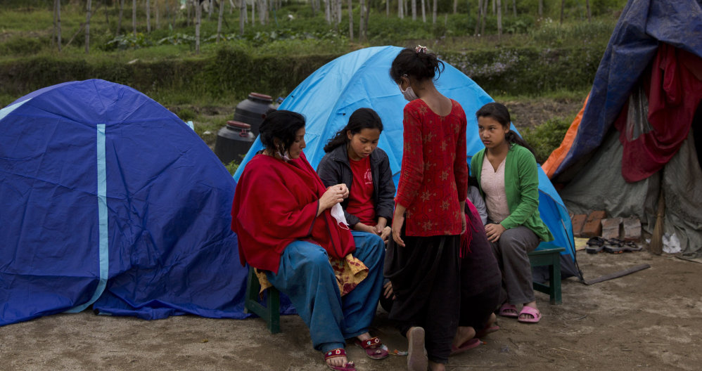 Nepalese villagers gather by tents where they have taken shelter in Sakhu, on the outskirts of Kathmandu, Nepal, on Wednesday. People fear being inside buildings.