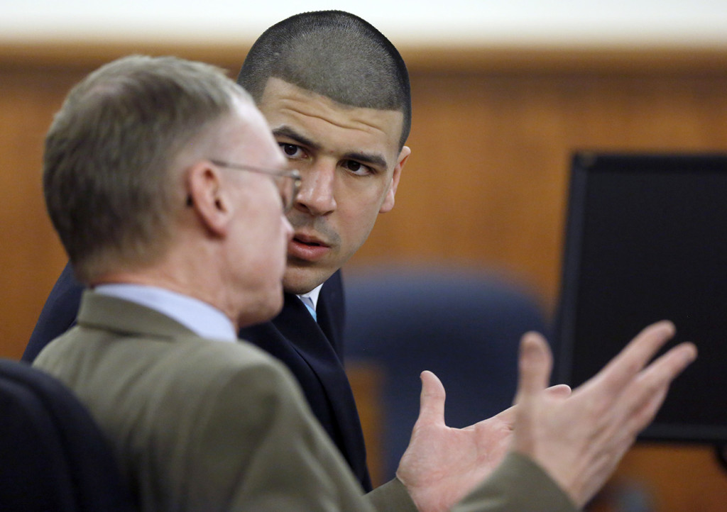 Aaron Hernandez listens to his defense attorney Charles Rankin as the judge and attorneys for both sides discuss questions from the jury deliberating Hernandez's fate, Thursday in Fall River, Mass. The Associated Press