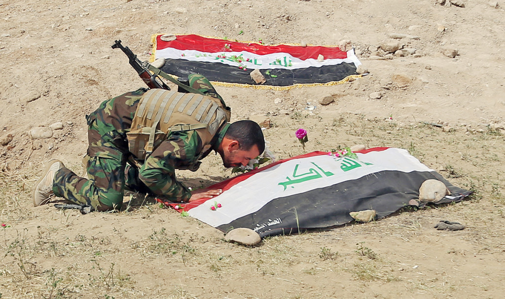 A Shiite militiaman kisses a grave on Friday at the site where Islamic State militants are believed to have buried  hundreds of Iraqi soldiers. The Associated Press