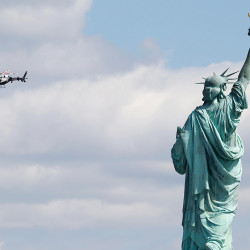 APRIL 24: A New York police helicopter circles the Statue of Liberty , which was evacuated after a report of a suspicious package Friday. Visitors posted photos online showing hundreds of people being herded toward a ferry landing. Tourists were taken off the ferries serving nearby Ellis Island and those vessels were used to evacuate Liberty Island. The Associated Press