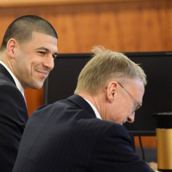 Former New England Patriots tight end Aaron Hernandez smiles with attorney Charles Rankin in the courtroom during the jury's first full day of deliberations in Hernandez' murder trial, on April 8, 2015. The Associated Press