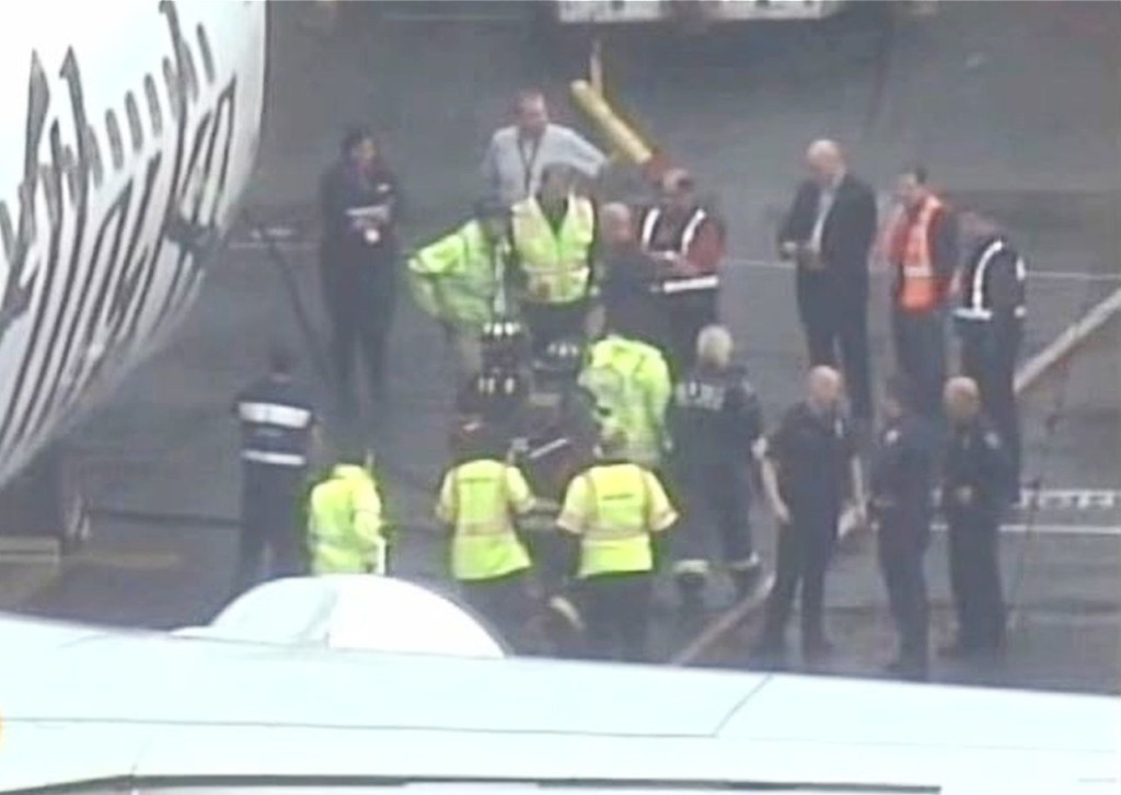 A Menzies Aviation  worker is escorted to the terminal at Seattle-Tacoma International Airport after he  was removed from the cargo hold of an Alaska Airlines passenger airplane on Monday. The Associated Press / KIRO image from video