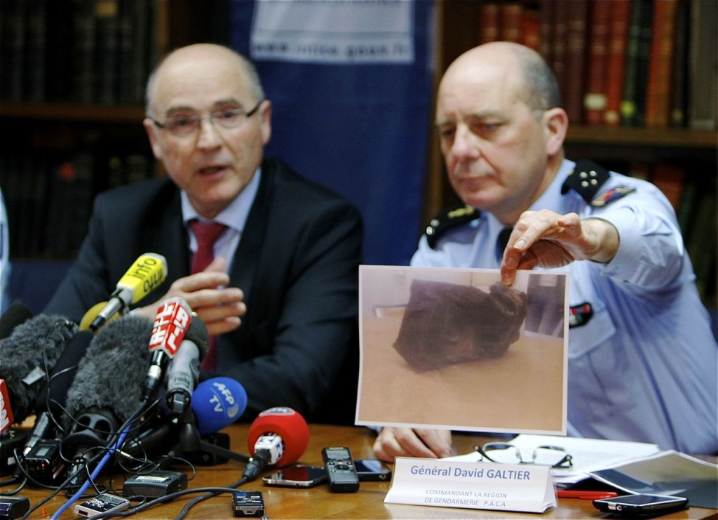Gen. David Galtier displays a photo of the second black box from the Germanwings plane that crashed in the French Alps last week. Marseille prosecutor Brice Robin, left, said a gendarme found the  box blackened and buried in the mountainside at the crash site Thursday. The Associated Press