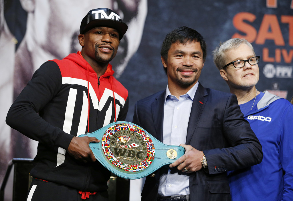 Boxers Floyd Mayweather Jr., left, and Manny Pacquiao pose with a WBC belt during a press conference Wednesday, April 29, 2015, in Las Vegas. Mayweather will face Pacquiao in a welterweight title fight in Las Vegas on May 2. At right is Freddie Roach, Pacquiao's trainer.