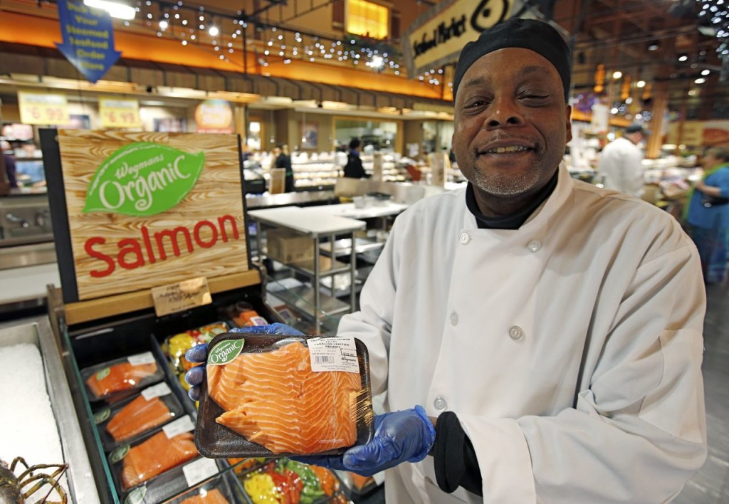 Cooking coach and chef Charles Hill holds a Canadian certified organic farm-raised King Salmon at the Wegmans, in Fairfax, Va., on Friday. The Associated Press