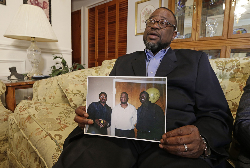 Anthony Scott holds a photo of himself, center, and his brothers Walter Scott, left, and Rodney Scott, at his home near North Charleston, S.C., Wednesday. Below: A closeup of Walter Scott in the same photo. The Associated Press