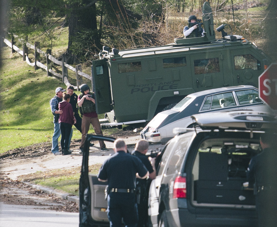 A woman is accompanied by Portland police near an armored vehicle after she left a house on Elizabeth Road where a shooting left one person seriously wounded and another in custody in Portland on Friday.