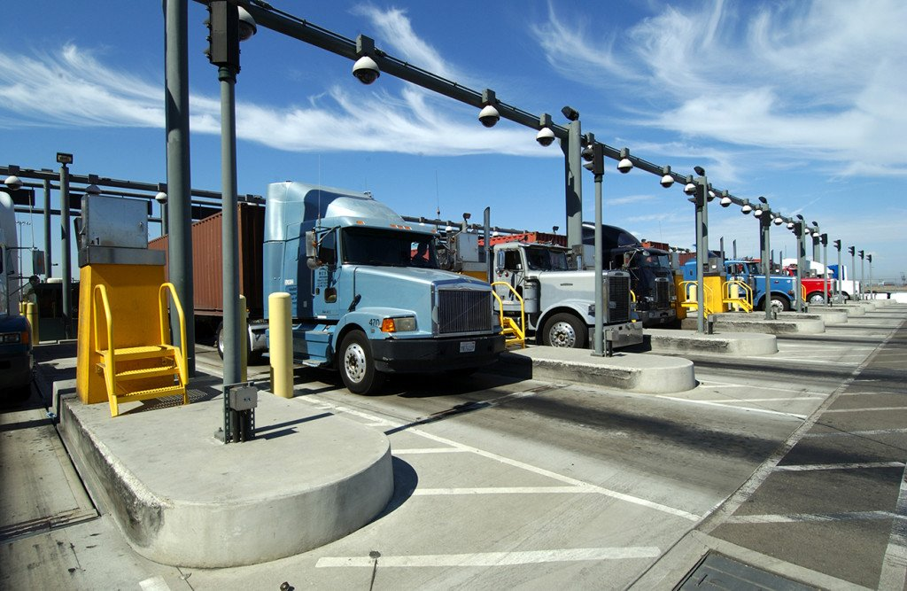 """Tractor-trailers pass through a checkpoint at the Port of Los Angeles in this courtesy photo. The Teamsters say drivers have been victims of """"persistent wage theft"""" from employers because they are treated as independent contractors instead of employees."""