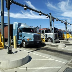 "Tractor-trailers pass through a checkpoint at the Port of Los Angeles in this courtesy photo. The Teamsters say drivers have been victims of ""persistent wage theft"" from employers because they are treated as independent contractors instead of employees."