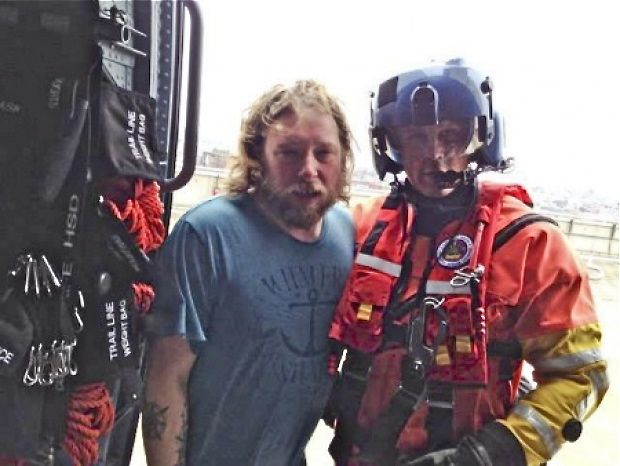 An unidentified man stands with a rescuer from the U.S. Coast Guard after the nine crew of the Liana's Ransom were saved. U.S. Coast Guard photo