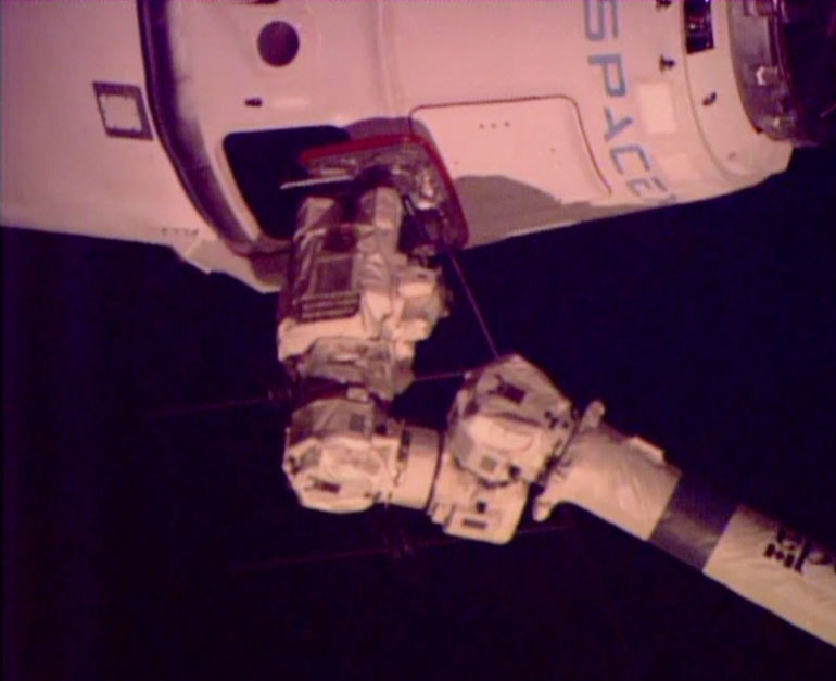 A robotic arm from the space station connects with the SpaceX Dragon freighter with its delivery of groceries, equipment and experiments. Photo courtesy of NASA TV
