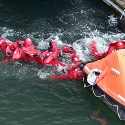 Fishermen learn how to group together while wearing immersion suits Thursday.