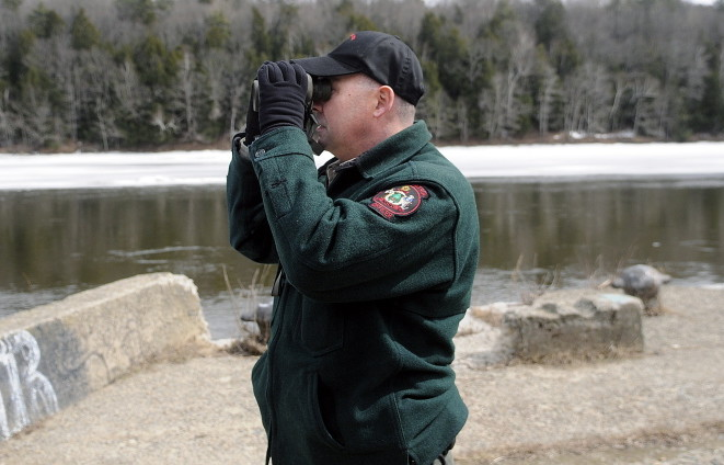 Marine Patrol Officer Clint Thompson scans the Kennebec River in Hallowell in April while searching for the remains of a woman who reportedly went under the ice in Augusta on March 21.