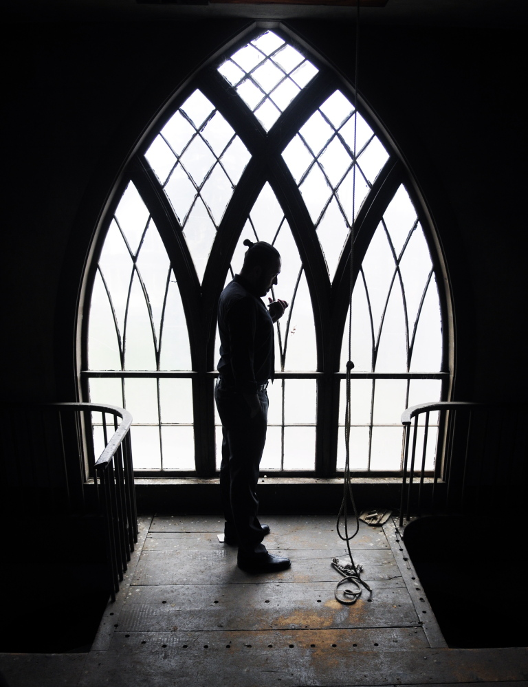 David Boucher stands in the bell tower talking on his cell phone to set up utilities in the former church that his company Lost Orchard Brewery bought to use as a tasting room on Thursday in Gardiner.