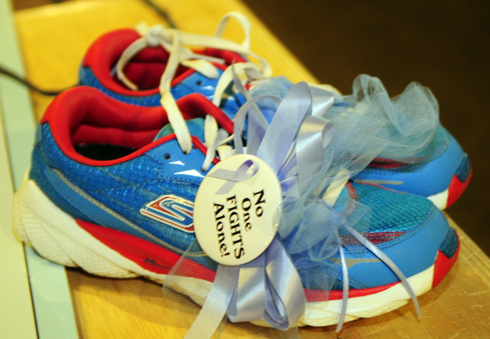 "These running shoes with a lavender ribbon and button that belonged to the late Nancy Tarr were ""retired"" and hung on the rafters Friday at Kennebec Valley Coaching in Augusta. The Miles for Mom fundraiser donated $1,200 to the Harold Alfond Center for Cancer Care."