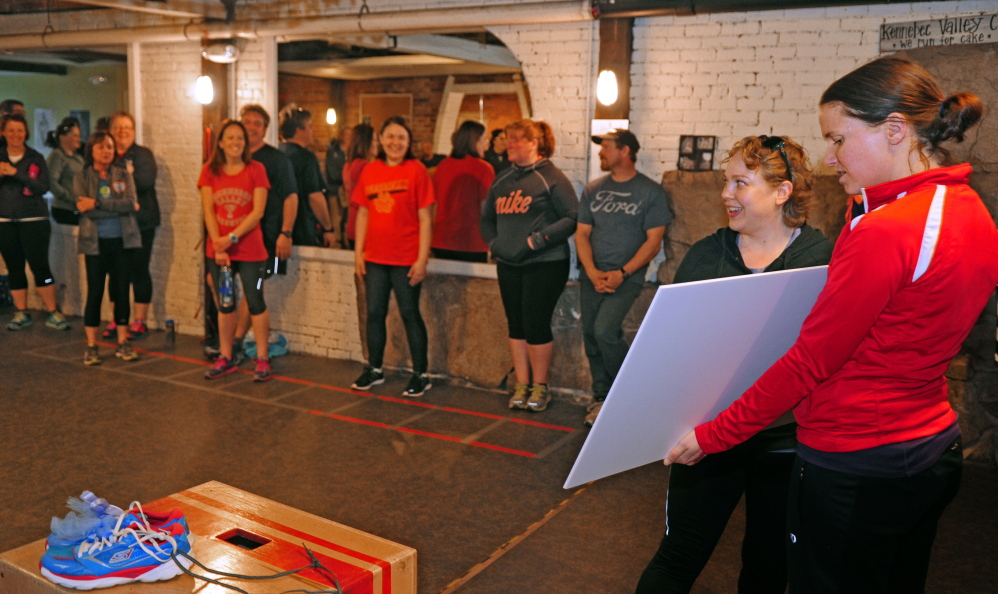 After the run/walk event, participants watch on Friday as Jessica Tarr fills in the amount on the large ceremonial cardboard check held by Amy Lawson at Kennebec Valley Coaching in Augusta. The Miles for Mom fundraiser donated $1,200 to the Harold Alfond Center for Cancer Care.
