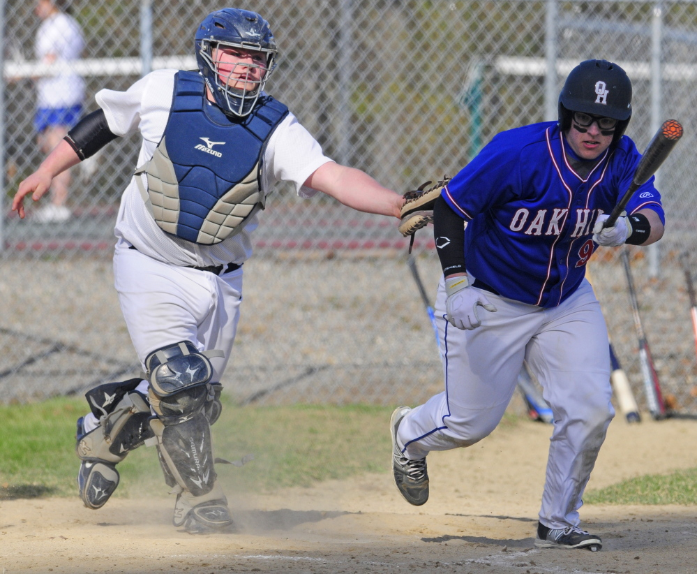 Dirigo catcher Tyler Frost, left, tags out Oak Hill's Adam Mooney as he tries to leg out a dropped third strike during a Mountain Valley Conference game Friday in Wales.