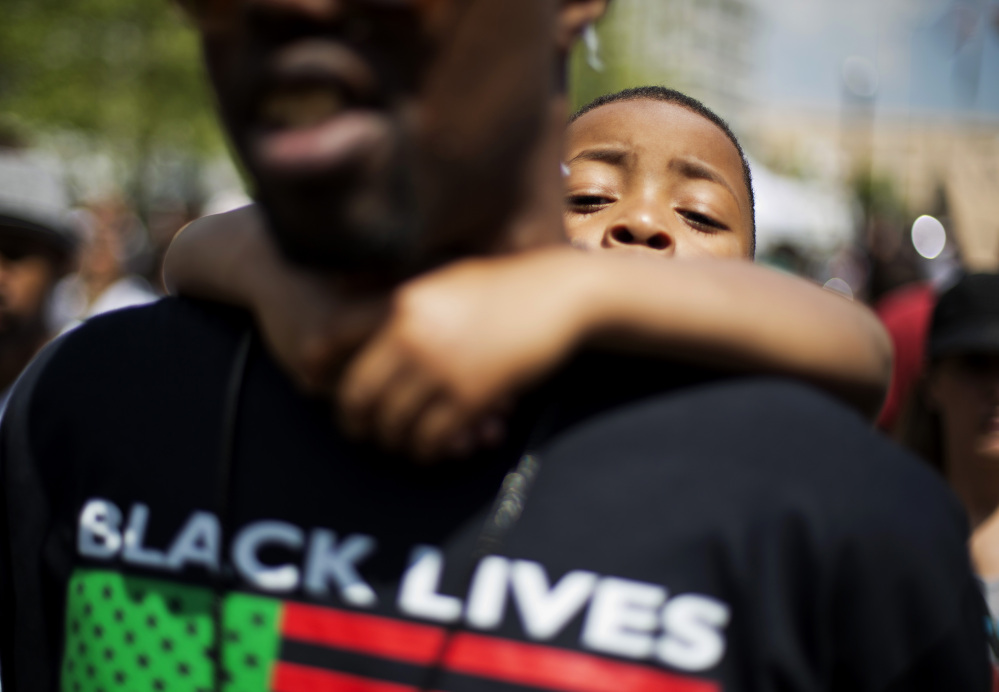 Devonte Reed, 5, right, looks over the shoulder of James Watson, both of Baltimore, while attending a demonstration at City Hall the day after charges were announced against the police officers involved in Freddie Gray's death on Saturday in Baltimore.
