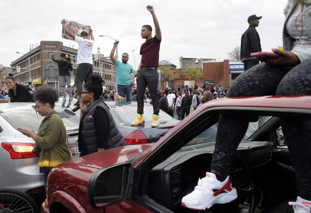 Protesters stand on cars near the intersection of North Avenue and Pennsylvania Avenue in Baltimore on Friday, the day of the announcement of charges against the police officers involved in Freddie Gray's arrest.