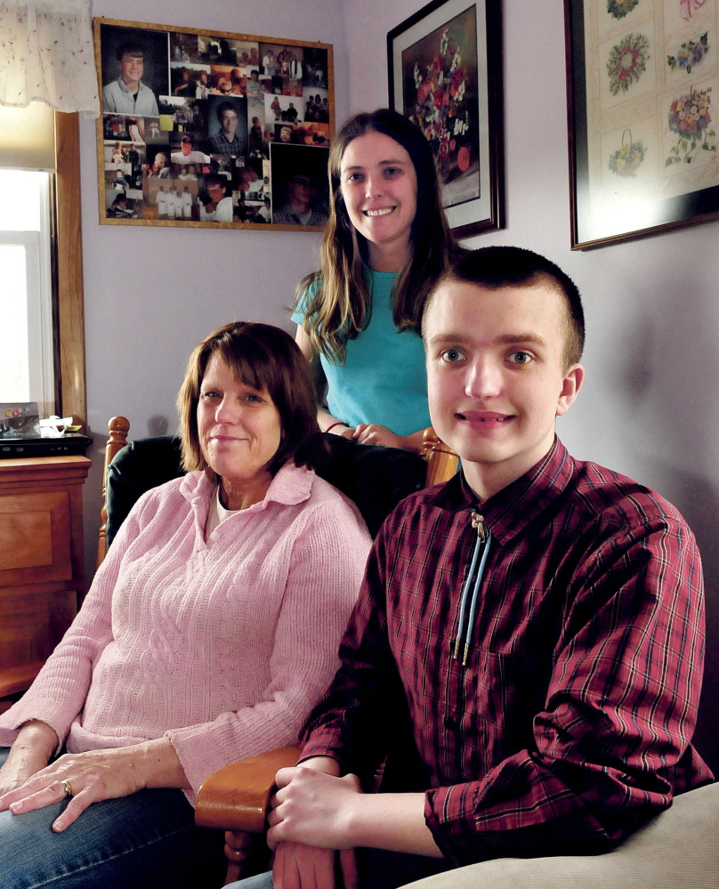 Yvonne Batson sits with her children Corina and Nathanael on Monday at their home in Fairfield. In the background are photographs of Yvonne's son Brendan, who died in 2001. The Batsons suffer from neurofibromatosis, a genetic disorder.