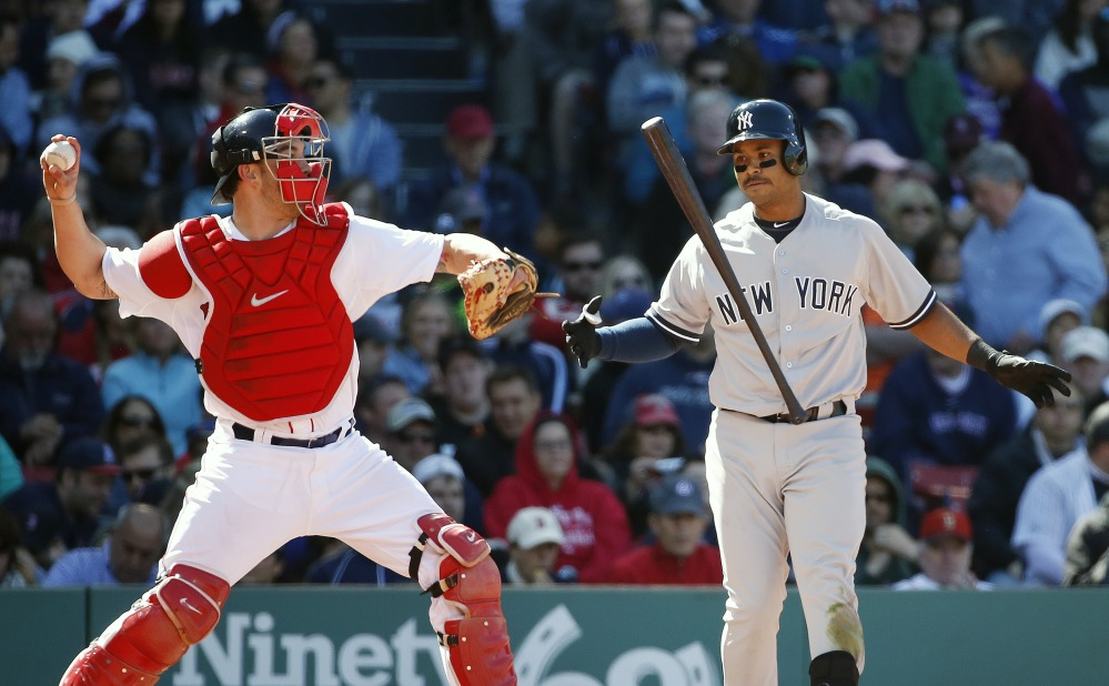 Boston Red Sox's Blake Swihart, left, throws back to the mound as New York Yankees' Gregorio Petit, right, tosses his bat after striking out during the seventh inning Saturday in Boston. Swihart collected his first hit in his major league debut but the Yankees won 4-2.