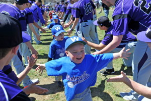 Members of a T-ball team high-five members of the Waterville Senior High School baseball team during Cal Ripken opening day ceremonies Saturday at Fran Purnell Field in Waterville.