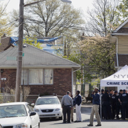 Residents stand in the doorway of their home as they watch police officers investigate the scene of a shooting in the Queens borough of New York, on Sunday. Demetrius Blackwell is accused of shooting a New York City police officer in the head Saturday evening and is being charged with two counts of attempted murder of a police officer.