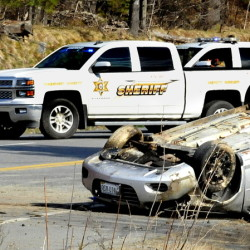 A firefighter walks past an overturned car Sunday on U.S. Route 201A in Norridgewock. The car's lone occupant died Sunday afternoon after the car hit an embankment and overturned twice at the Ward Hill Road intersection.