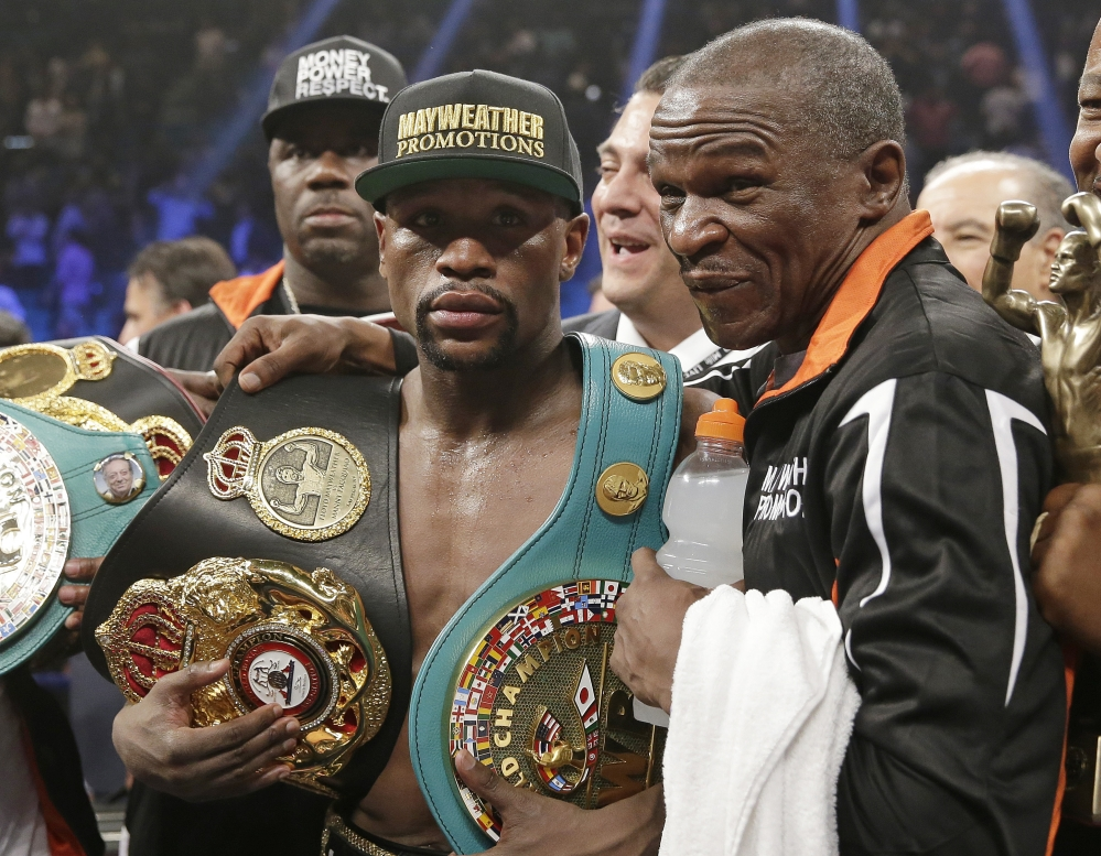 AP photo Floyd Mayweather Jr., left, poses with his champion's belts and his father, head trainer Floyd Mayweather Sr., after his victory over Manny Pacquiao  in their welterweight title fight Saturday in Las Vegas.