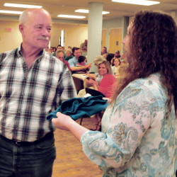 Mid-Maine Homeless Shelter volunteer coordinator Cindy Burns presents a shirt to volunteer John Maddux on Sunday in recognition for his time and effort at the Waterville facility. The presentation took place during a volunteer celebration and annual meeting.